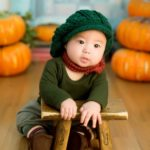baby in front of fall pumpkins